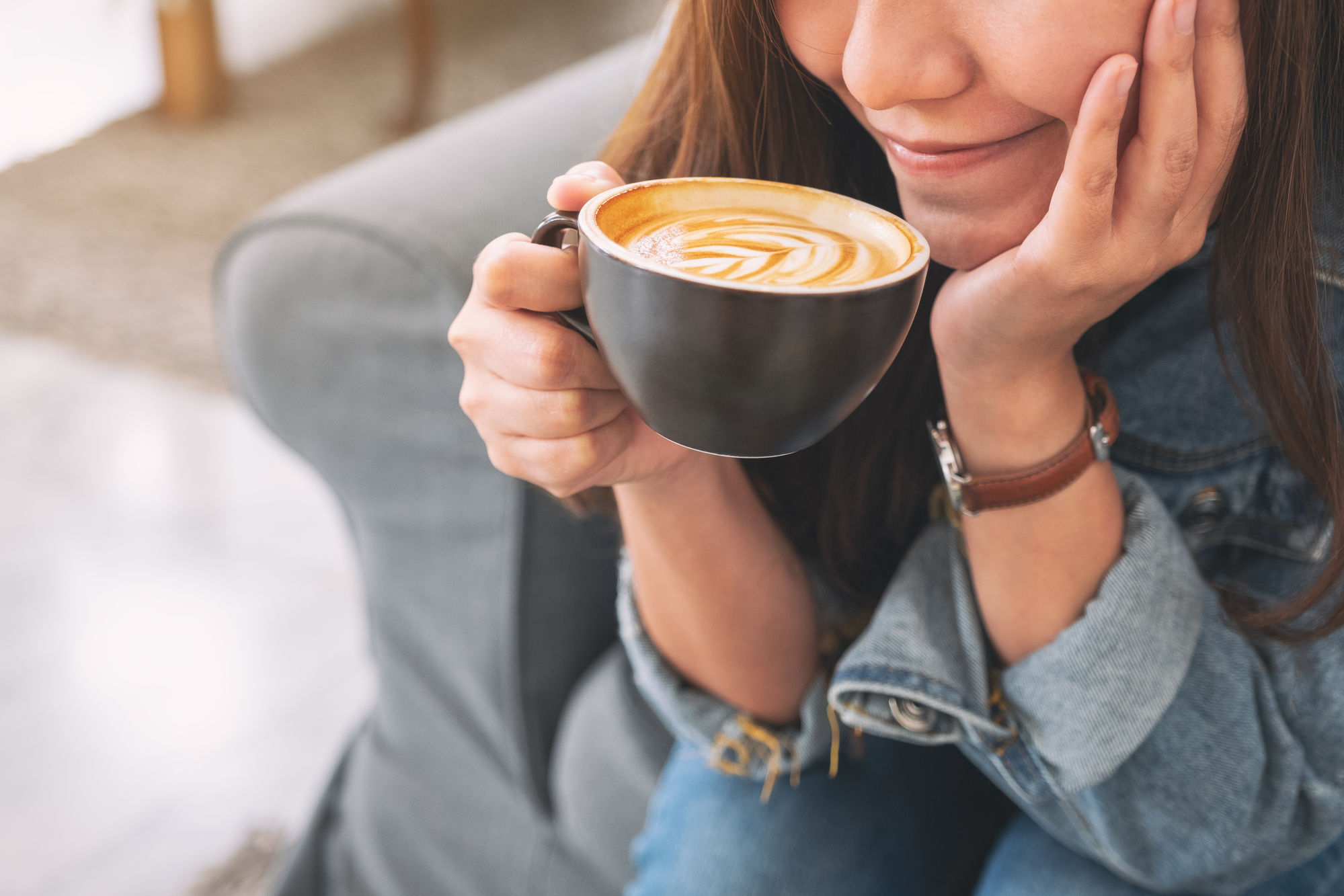 Woman sitting on a couch, sipping her coffee